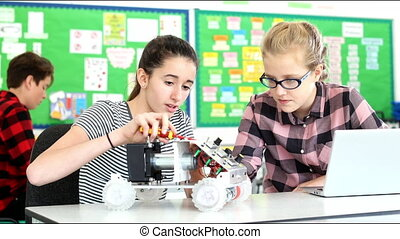 Two Female Pupils Building Robotic Car In Science Lesson -...
