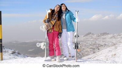 Two female snowboarders standing on a mountain