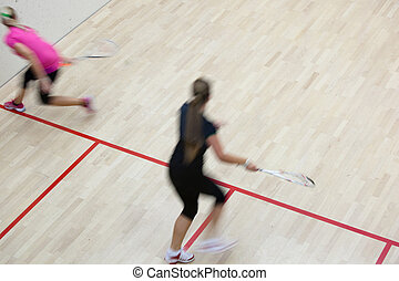 Two female squash players in fast action on a squash court...