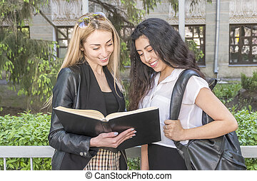 two female students are reading a book