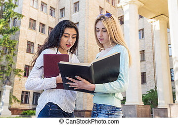 two female students study textbook