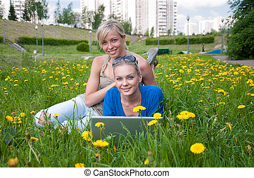 Two female students with a laptop in the park