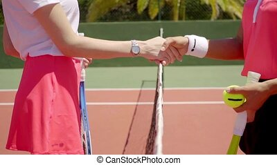 Two female tennis opponents shaking hands