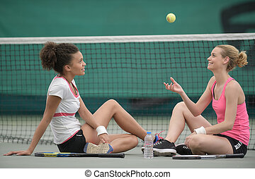 two female tennis player relaxing on the court