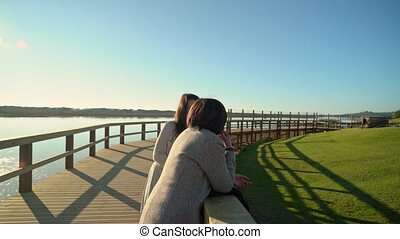 Two females communicate on a boardwalk near a river shore. High quality 4k footage