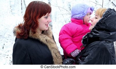 Two females talks in park, one holds kid on hands