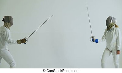 Two fencers have fencing match on white background indoors -...