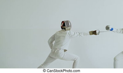 Two fencers have fencing training on white background...