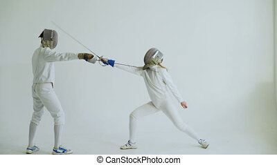 Two fencers having training attack exercises in fencing on...