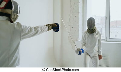 Two fencers having training attack exercises in fencing in...