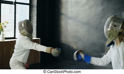 Two fencers man and woman have fencing match indoors - Two...