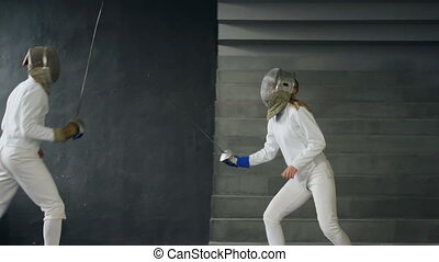 Two fencers man and woman shake hands each other at the end of fencing competition indoors