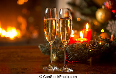 Two filled champagne glasses in front of Christmas wreath with burning candles