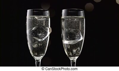 Two filled glasses of champagne with an ice cube in each....