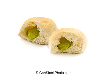 Two filling bun bread cut in half to show green custard on white background