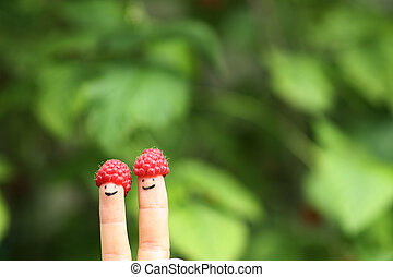 two fingers with funny faces in raspberry hats on green bush background
