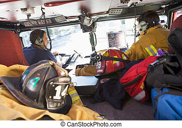 Two firefighters driving a fire engine with gear in the back...