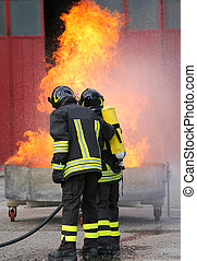 two firefighters during the exercise with a tank full fire and t