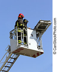 two firefighters in the cage of fire engine