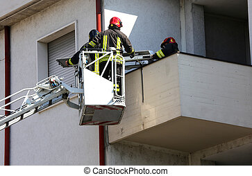 two firefighters in the elevated cage of fire engine - two...