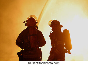 two firefighters - Two firefighters are silhouetted against...