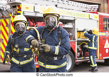 Two firefighters with hose and axe walking away from fire engine and another firefighter in background (selective focus)