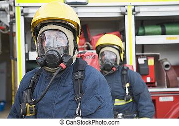 Two firemen in masks standing near fire engine (depth of field)