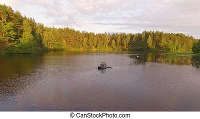 Two fisherman in rubber boat floats with white swan. Drone aerial shot. Friends relaxes in boat on lake in sunny forest. Stracha river, Belarus. Beautiful amazing european belarusian nature