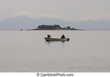 Two Fisherman on Foggy Alaska Waterway - Two fisherman in a...