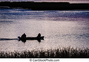 Two fishermen in the boat on a lake in the early morning sunrise, selective focus