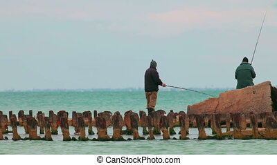 Two fishermen on rusty pier