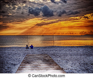 two fishermen on the sand at sunset in hdr
