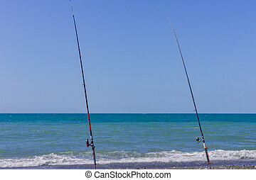 two fishing rods on sea beach. Fishing tourism and vacation concept