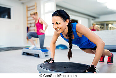Two fit attractive women in gym doing various exercises -...