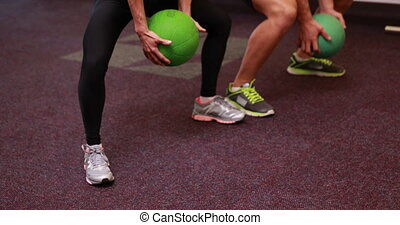 Two fit people squatting with medicine balls at the gym