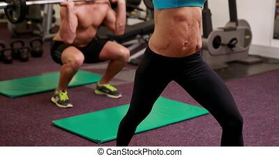 Two fit people working out at crossfit session at the gym