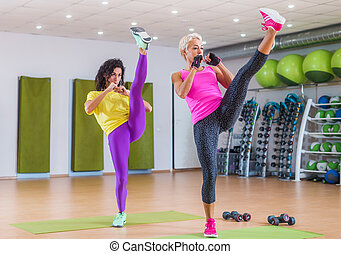 Two fit women doing straight leg kicking exercise while working-out in gym