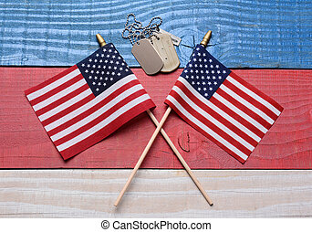 Two Flags and Dog Tags on Patriotic Table - Two crossed...