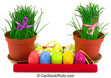 Two flowerpots with fresh grass and row of multicolor Easter eggs on the red mat