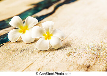 Two Flowers are on wooden texture background.