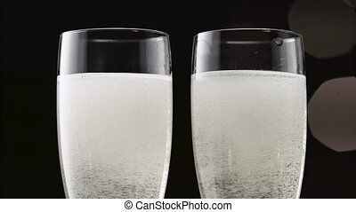 Two flutes of champagne with ice on the bottom. Bokeh...