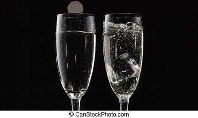 Two flutes of champagne with transparent pieces of ice on...