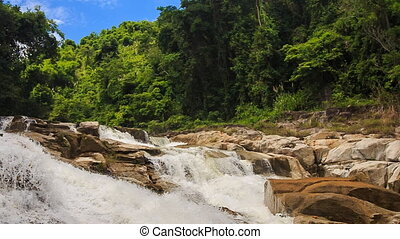 two foamy mountain streams against tropical plants blue sky