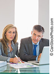 Two focused mature business people looking at camera trying to understand figures at office