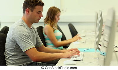 Two focused students working on computer