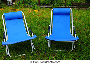 two folding deck chairs on the grass