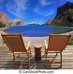 Two folding wooden chairs and the mountain lake
