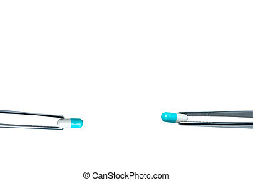 Two forceps pick white-blue capsule pills. Drugs choose for test in lab. Antibiotic drug selection. Antibiotic drug resistance concept. QA and QC in pharmaceutical factory concept. Drugs of choice.