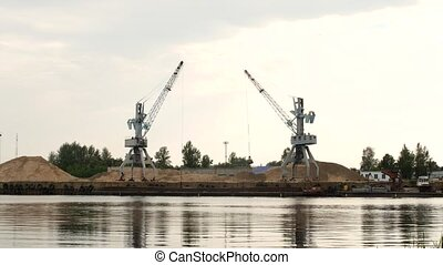 Two freight cranes in the port produce river sand, barge, port