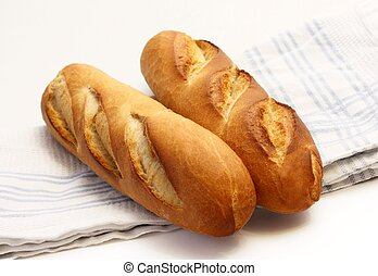 Two fresh baguettes - Two long narrow french loafs laid on ...
